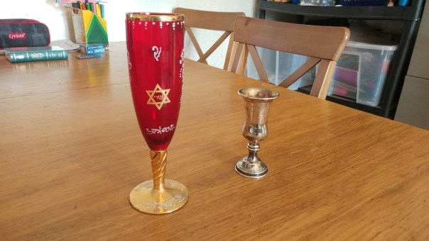 photo of two goblets; on the left, tall goblet made of red glass painted with gold and white trim; on the right, small silver goblet