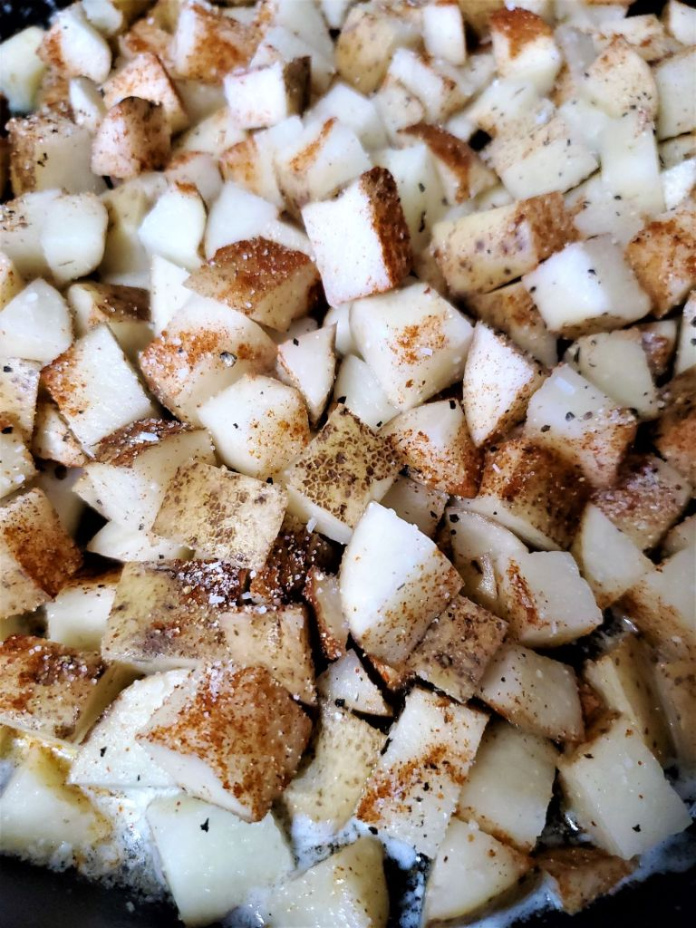 cubed potatoes in cast iron skillet