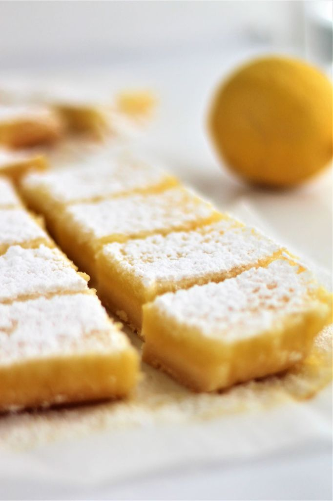 gf lemon bars in a row with a whole lemon in the background