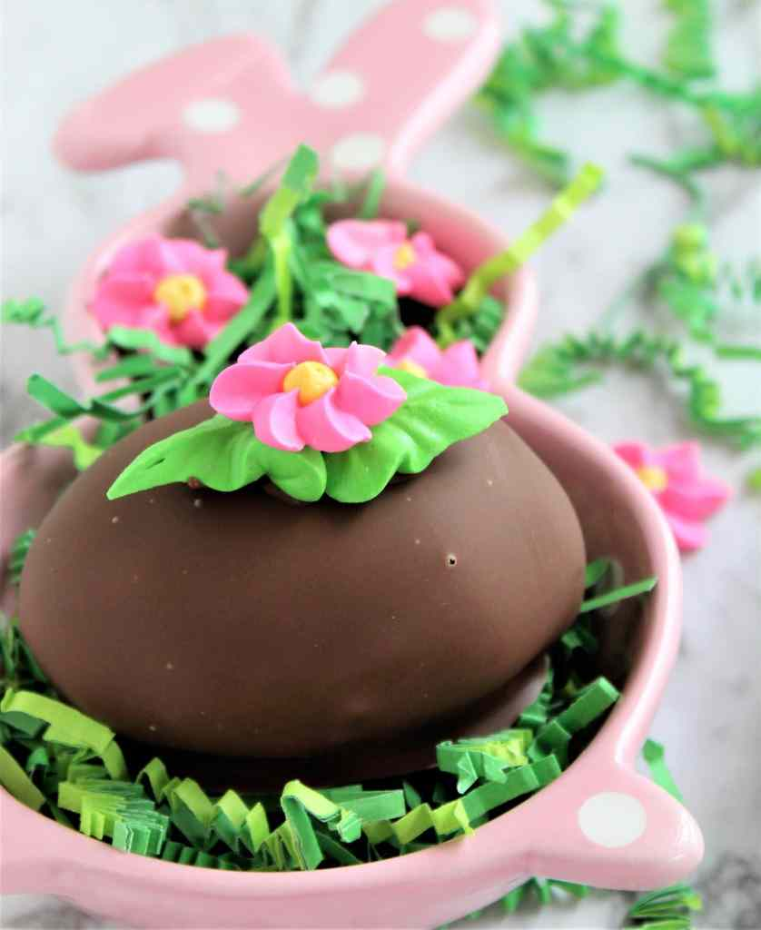 chocolate easter egg in pink bunny dish with green easter grass