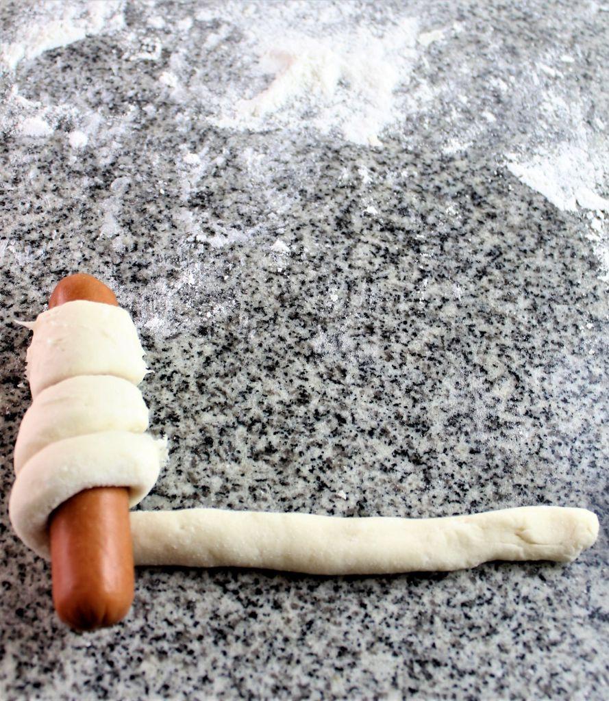 almost done rolling pretzel dough around hot dog
