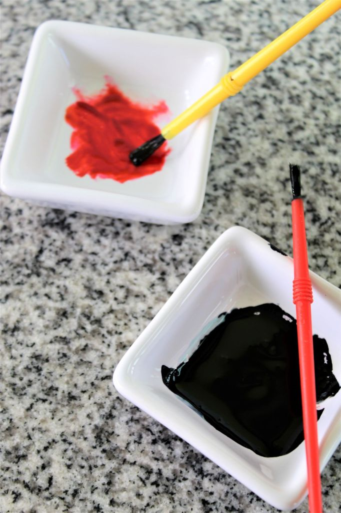 black and red gel food colors in small white square bowls