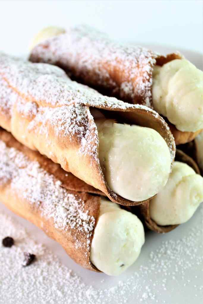 gluten free cannoli stacked on white cake plate