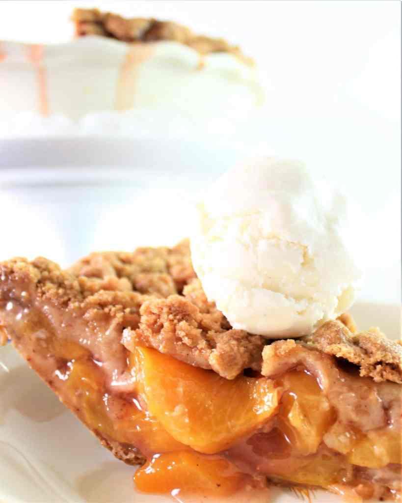 slice of gluten free peach crumb pie with vanilla ice cream scoop