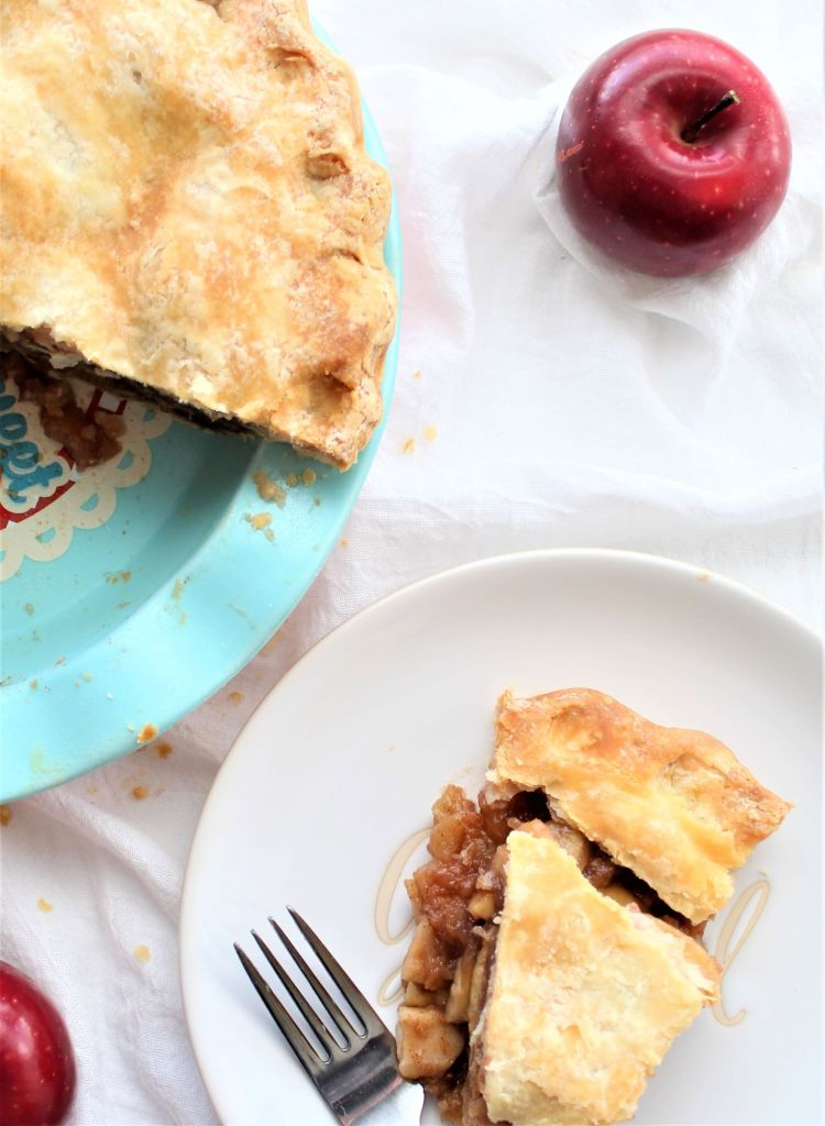 overhead shot of whole pie and slice with red apples on white background