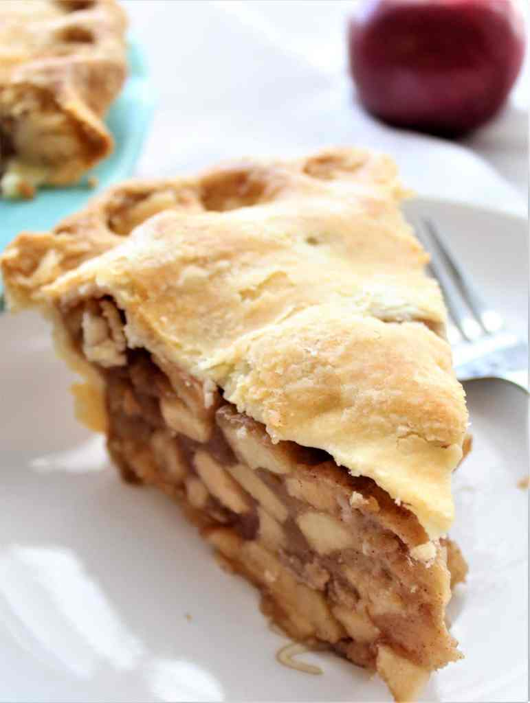 gluten free apple pie slice on white plate with red apple in background