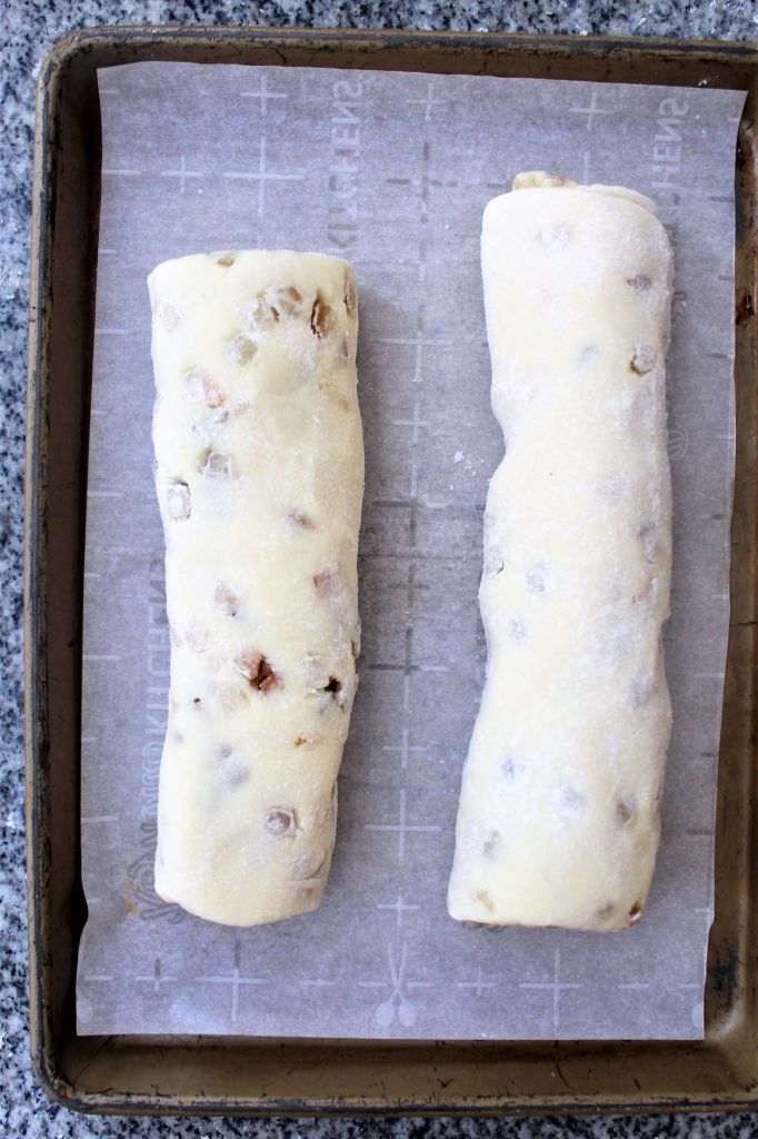 rolls of filled dough on a parchment lined baking sheet