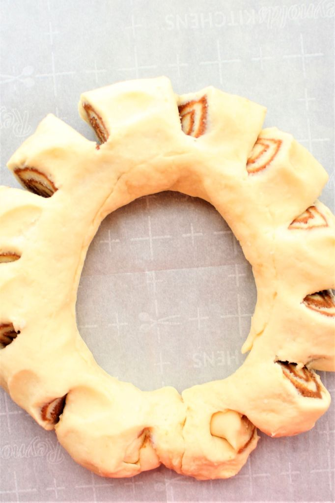 cuts made into dough roll to resemble wreath