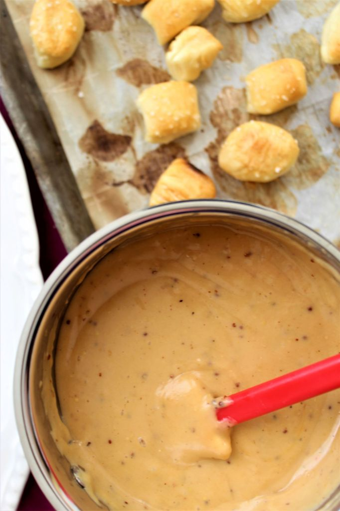 beer cheese dip in saucepan with soft pretzel bites in the background