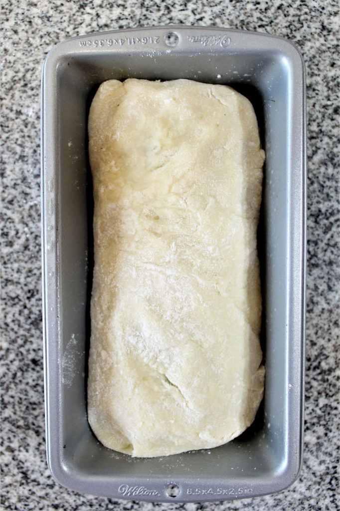 putting gf cinnamon raisin bread dough in pan