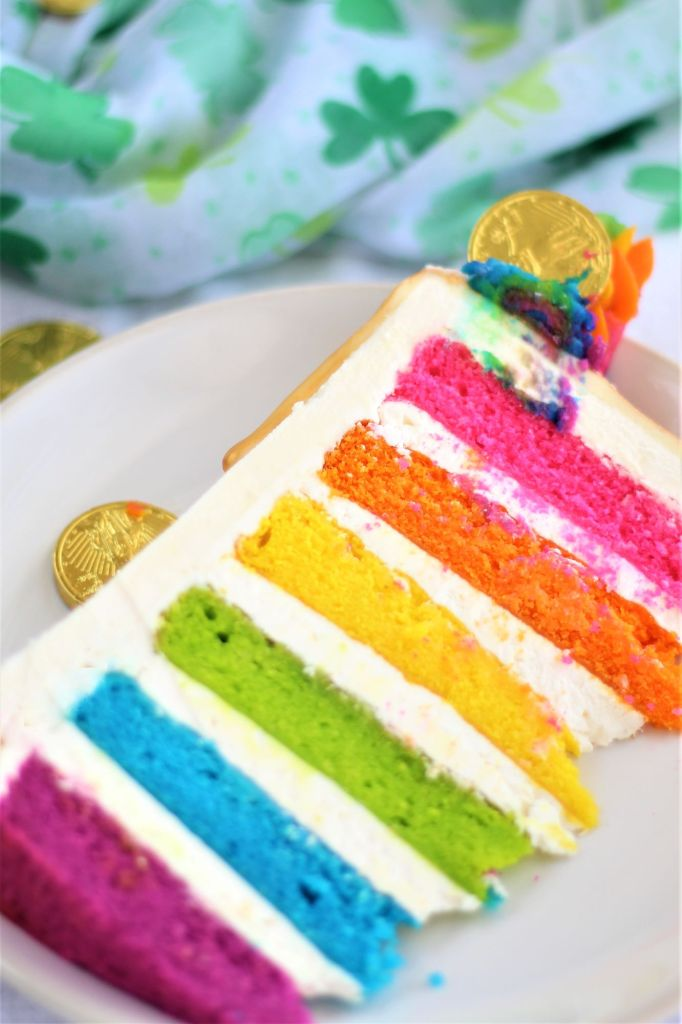 large slice of rainbow cake tipped over on plate