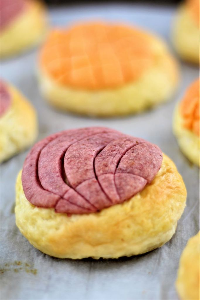 pinkish purple and orange gf conchas on parchment lined baking sheet
