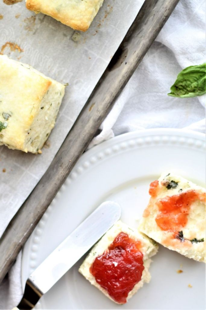 flat lay of strawberry covered basil cream biscuit with other biscuits on sheet tray