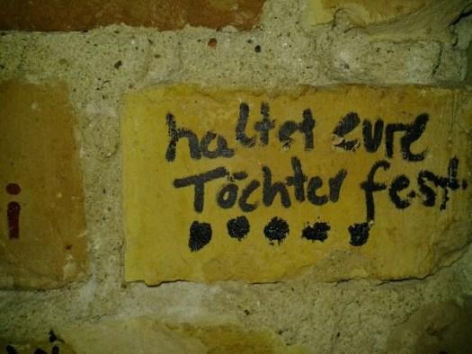"""""""haltet eure töchter fest"""" auf einer ziegelwand graffitiert"""