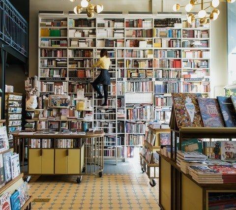 Libreria a doppia altezza strabordante di libri, il sogno di ogni lettore