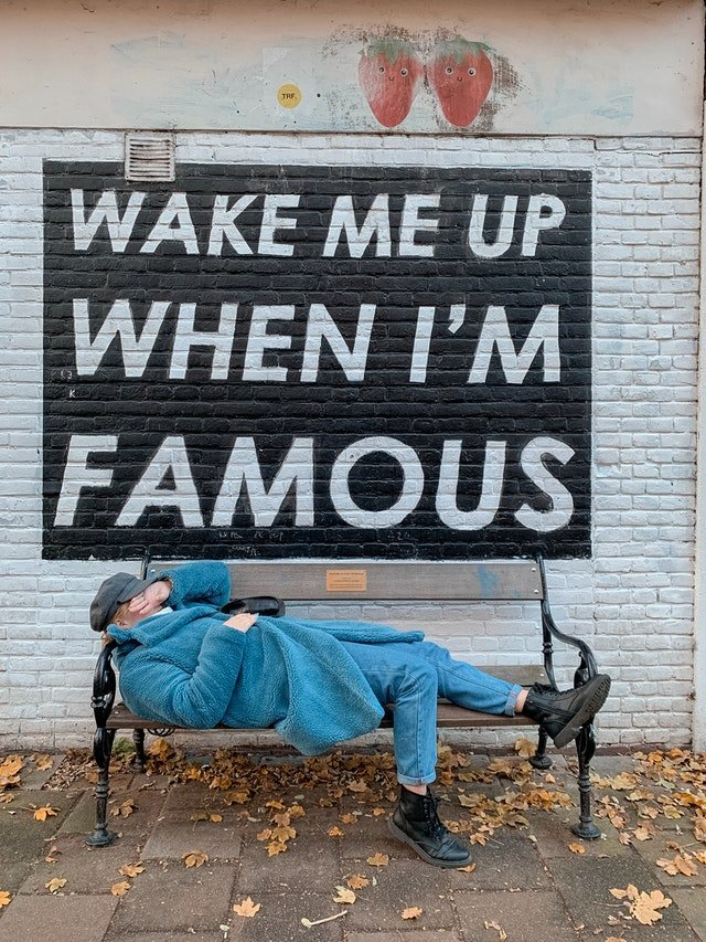 """Chi sono. Foto spassosa con uomo che dorme con accanto un muro dove c'è scritto """"svegliatemi quando sarò diventato famoso"""""""