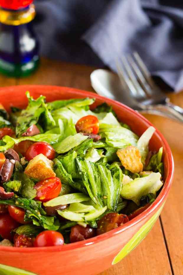 Vegan Italian panzanella salad with lettuce, Kalamata olives, and cherry tomatoes, with pan-crisped crunchy croutons to soak up the red wine vinegar, tomato, and olive oil juiciness. Toss in chickpeas for a light main course salad.