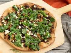 baked Caramelized Mushroom and Arugula Pizza Bianca on wooden peel, horizontal shot