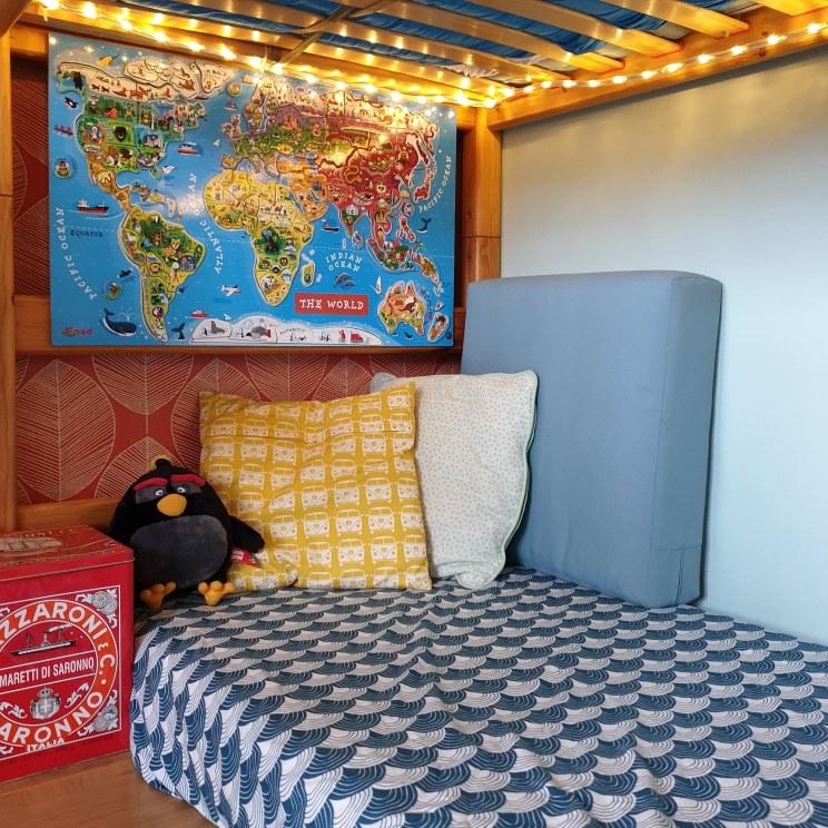 Kinderkamer inspiratie: retro jongenskamer met hout, blauw, rood en geel - hoeslaken van swedish linens en magnetische wandkaart van janod