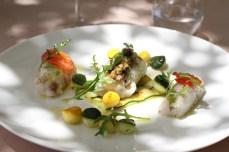 Le Loup de Méditerranée, le pavé cuit vapeur, damier de courgettes vertes et jaunes, condiments et jeunes pousses