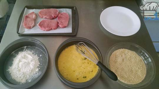 A breading station set up for pork chops, consisting of flour, beaten egg, and breadcrumbs.