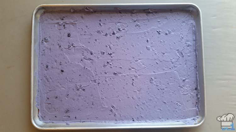 Blueberry joconde sponge cake batter spread evenly in the basin of a shallow small rectangular baking tray.