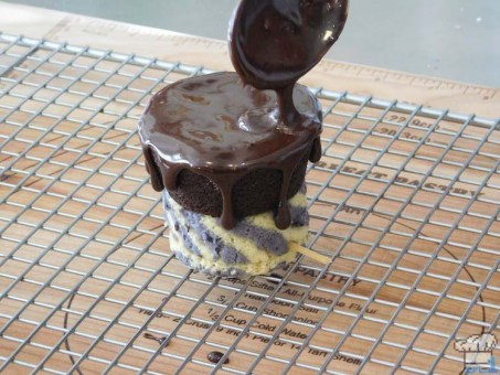 Spooning the warm chocolate fudge over the top of the chocolate cupcake to create slow drips down the side of the Legend of Zelda Spirit Tracks cannon car.