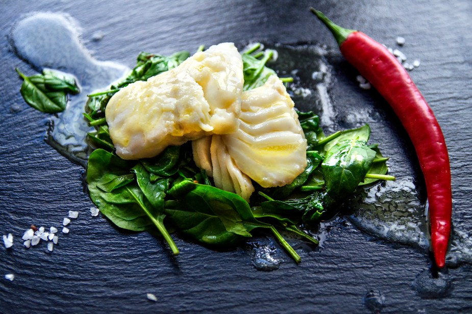 Delicious sea fish fillet with fresh healthy spinach and chili - Stock image