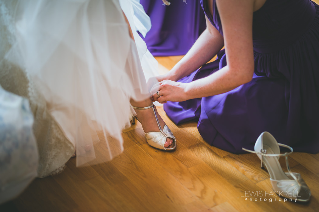 bridesmaid helping put on brides shoes