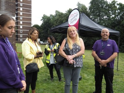 Members of Lewisham Homes staff stand next to a gazebo in front of Rosemount Point on the Dacres Estate