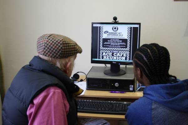 A young man helps an older man with a computer.