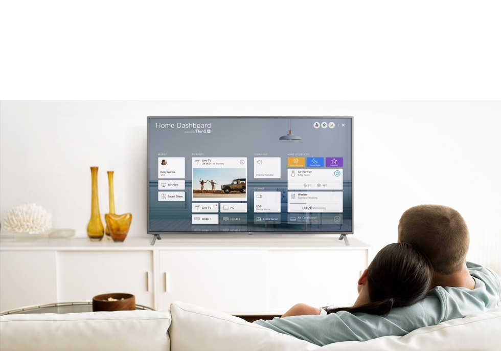 A men and women sitting on a sofa in the living room with the Home Dashboard on the TV screen.