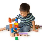 Little boy building a tower with colorful wooden blocks. Studio shot, isolated on white.