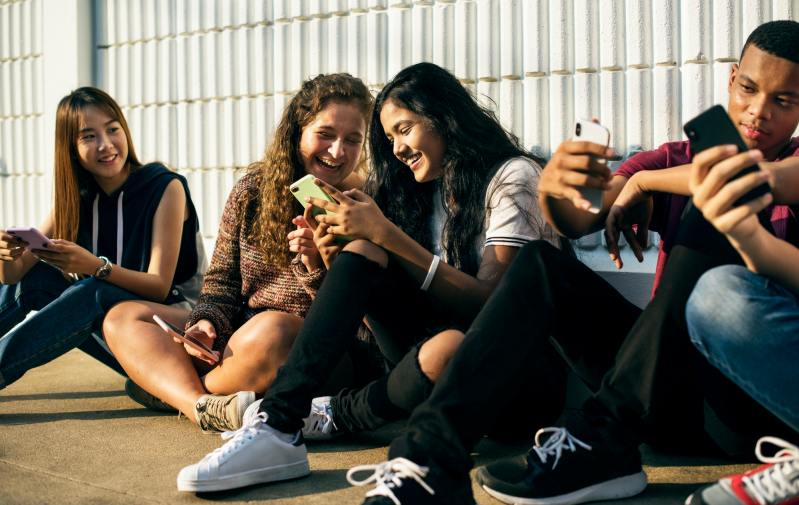 Group of young teenager friends chilling out together using smartphone social media concept
