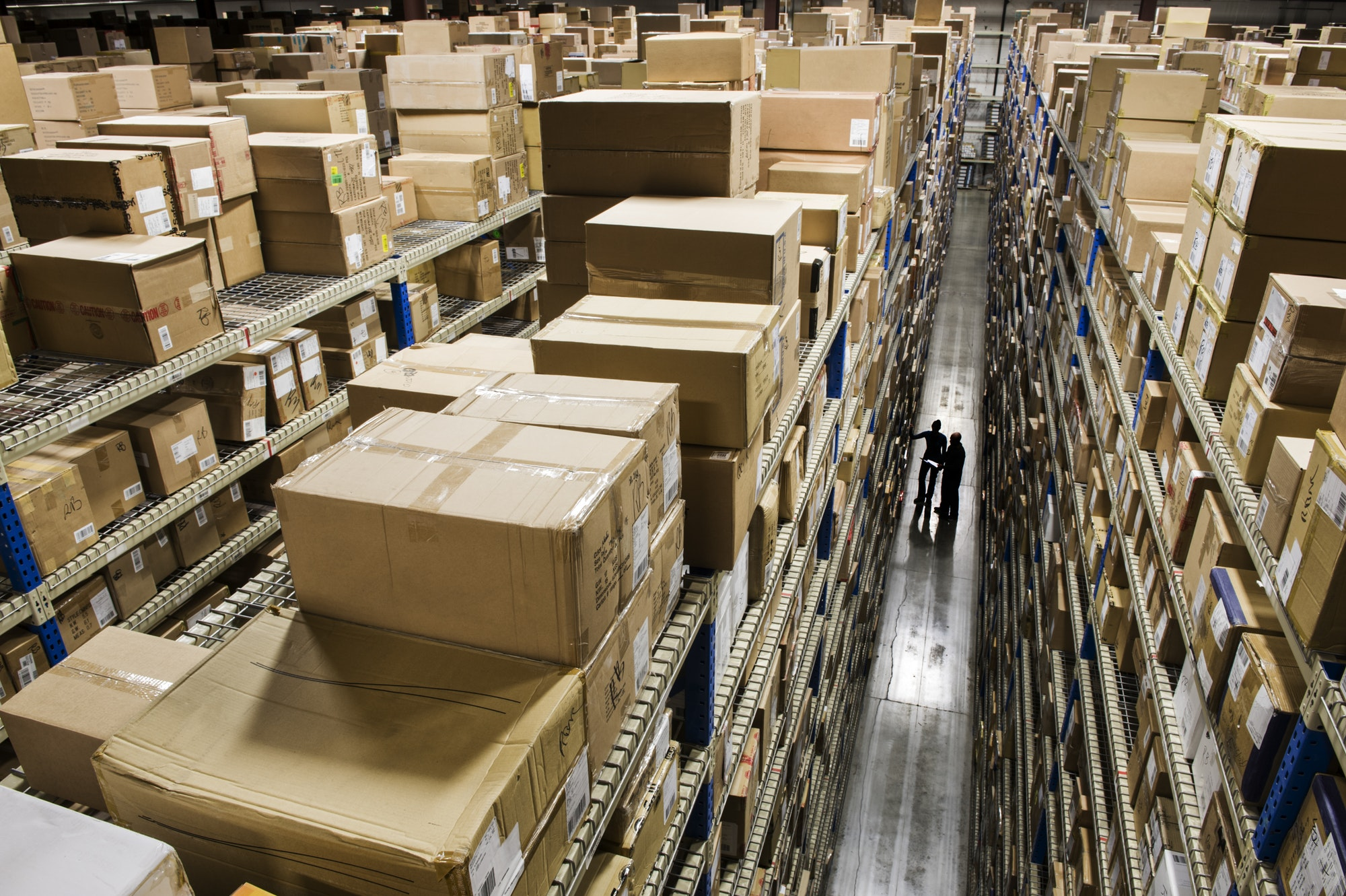 Looking down and over racks of products stored in boxes in a distribution warehouse.
