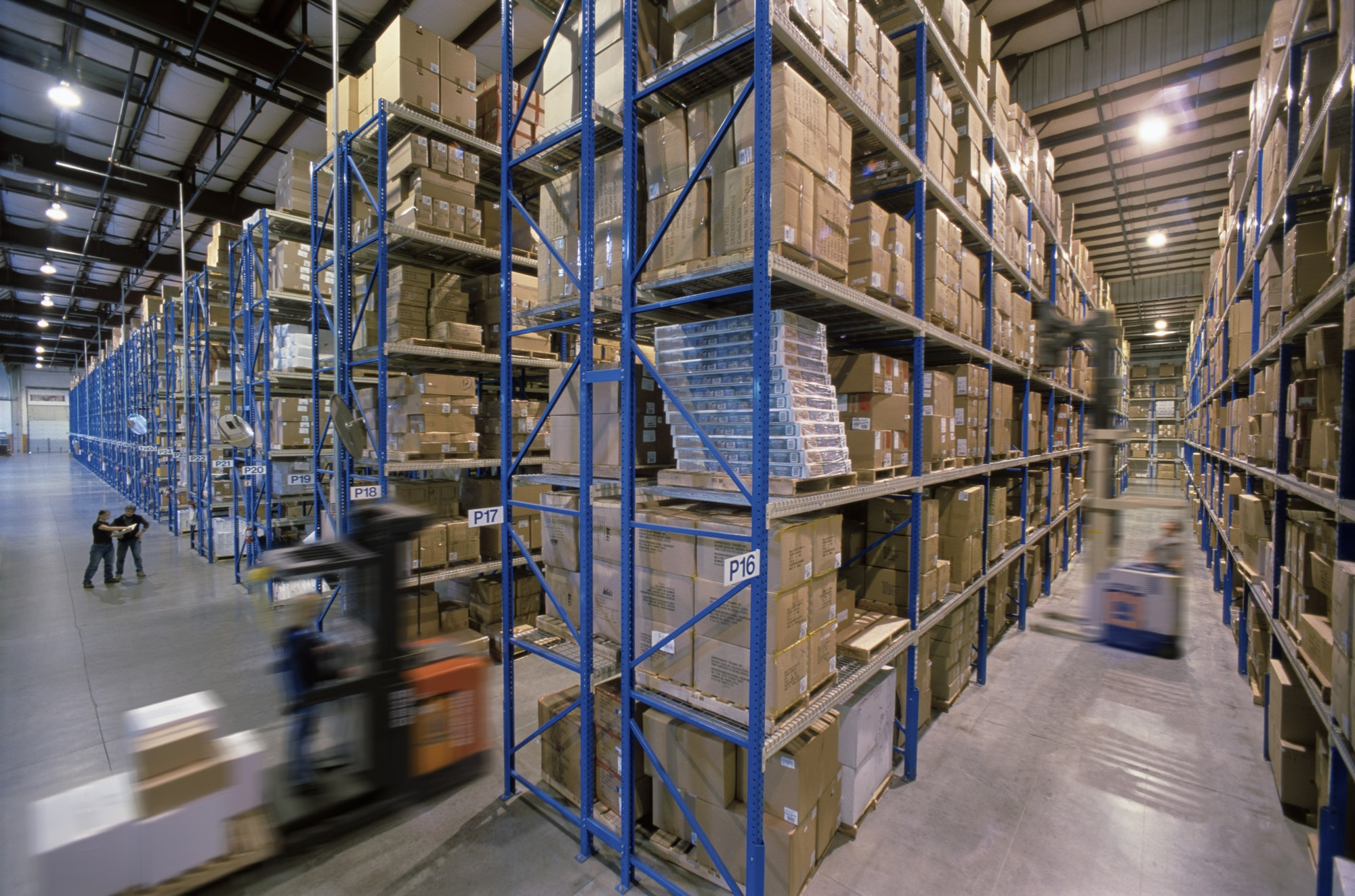 Overview of a large industrial distribution warehouse storing products in cardboard boxes on