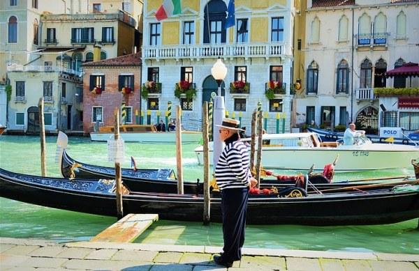 Photo de Venise: un gondolier de Venise sur les bords de l'eau qui attend les touristes en soif de clichés