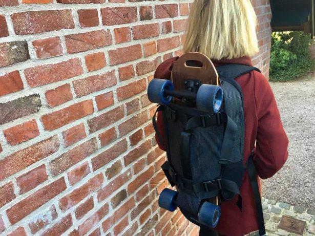 Le skate électrique peut lui aussi se caler sur le dos du sac à dos - Photo elwing boards