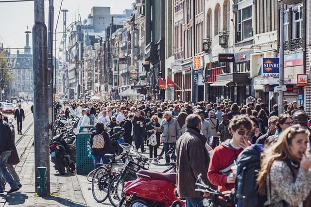 Crowd walking on the sidewalk.