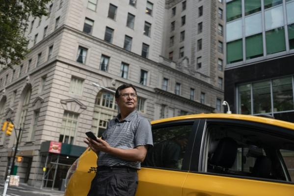 Serious ethnic man standing near taxi car with smartphone