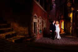 Bride and groom walk down alleyway at night