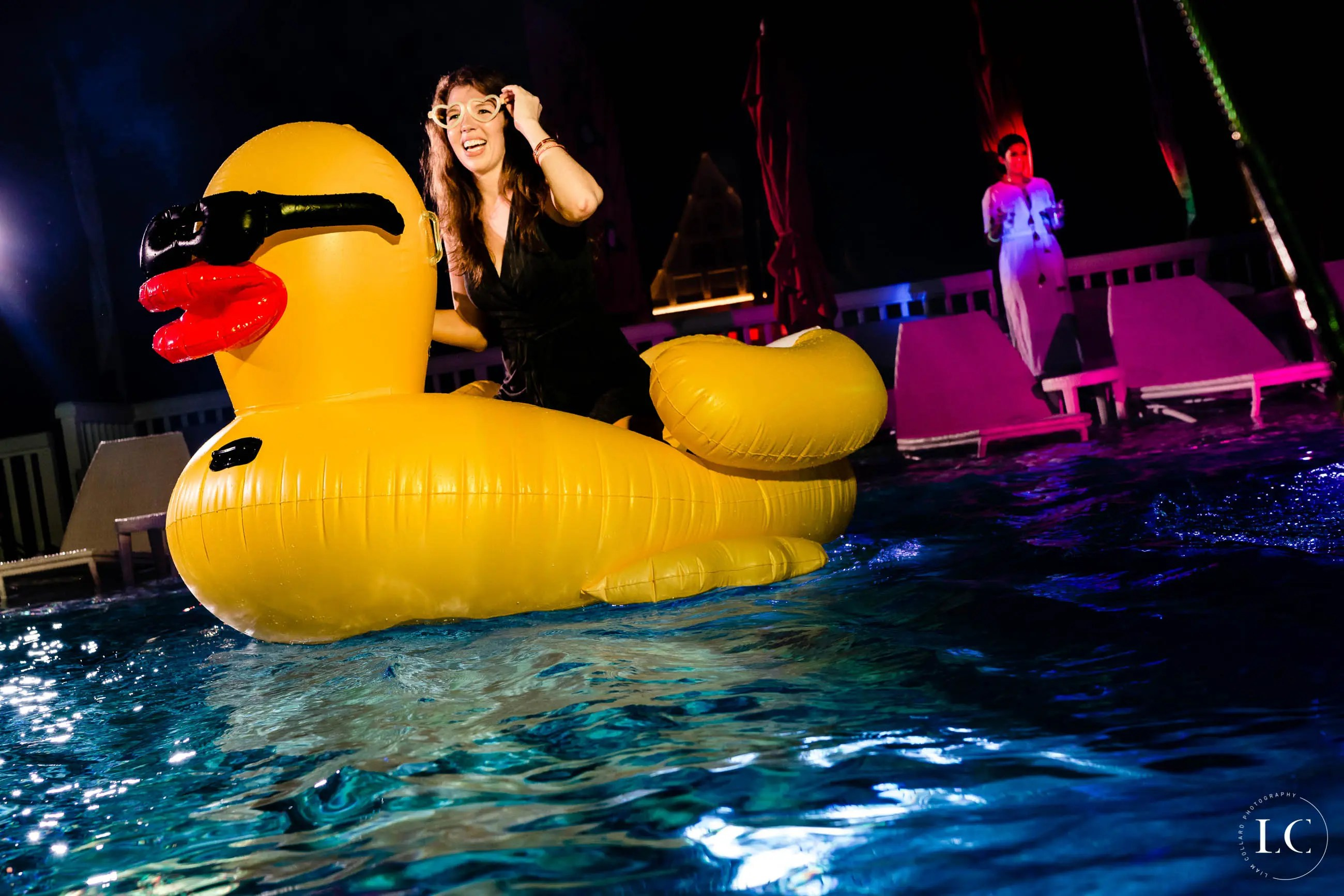 Woman on big rubber duck in a pool