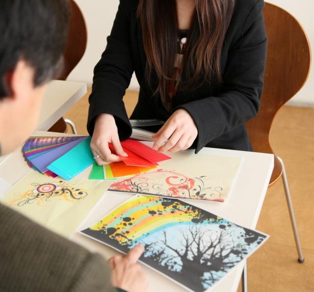 広告の色を検討するクリエイティブ・ディレクターとデザイナーの写真