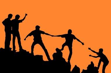 Tre mennesker som hjelper hverandre opp en bakke og to som heier på dem.