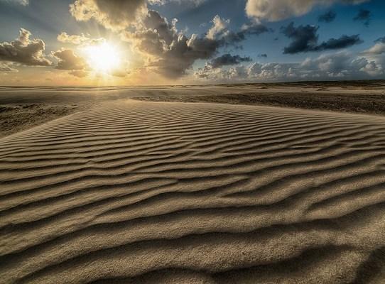 Beautiful shot of the sun rising over a sandy beach at the seashore