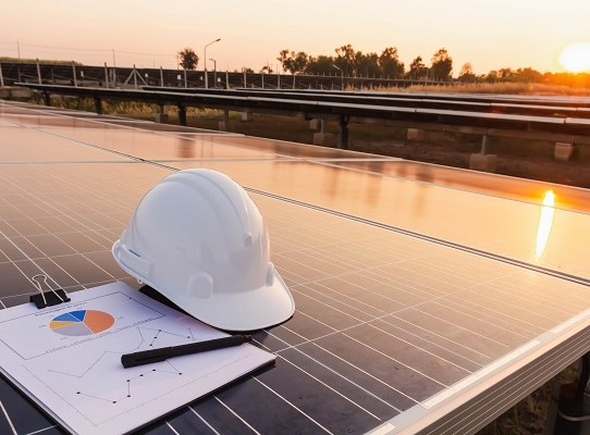 Engineers hat and the graph are placed on the solar panel, alternative electricity source, concept of sustainable resources