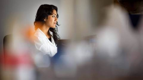 Researcher wearing white coat in lab