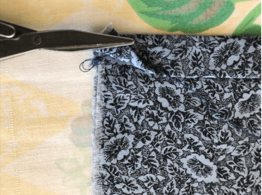 Tuck the knot of thread between layers of fabric to hide it
