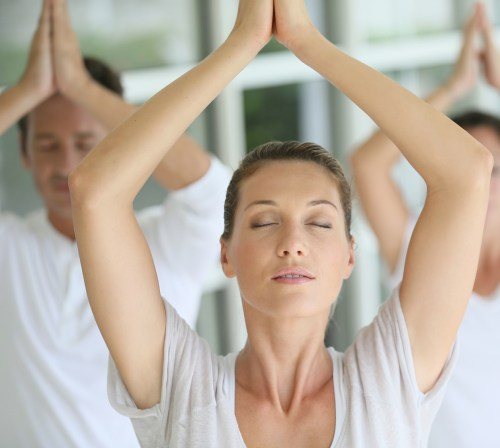 Attractive blond woman attending yoga course with groupKSNCùkcnqskn