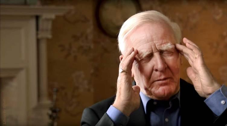El escritor británico John le Carré con los ojos cerrados y las manos masajeando sus sienes